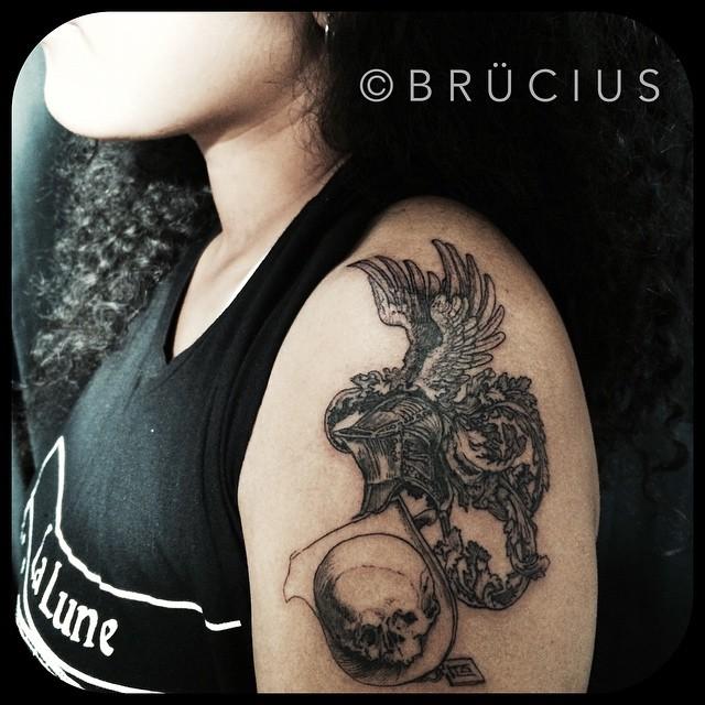 Skull Holding Gryphon Shoulder tattoo by BRÜCIUS