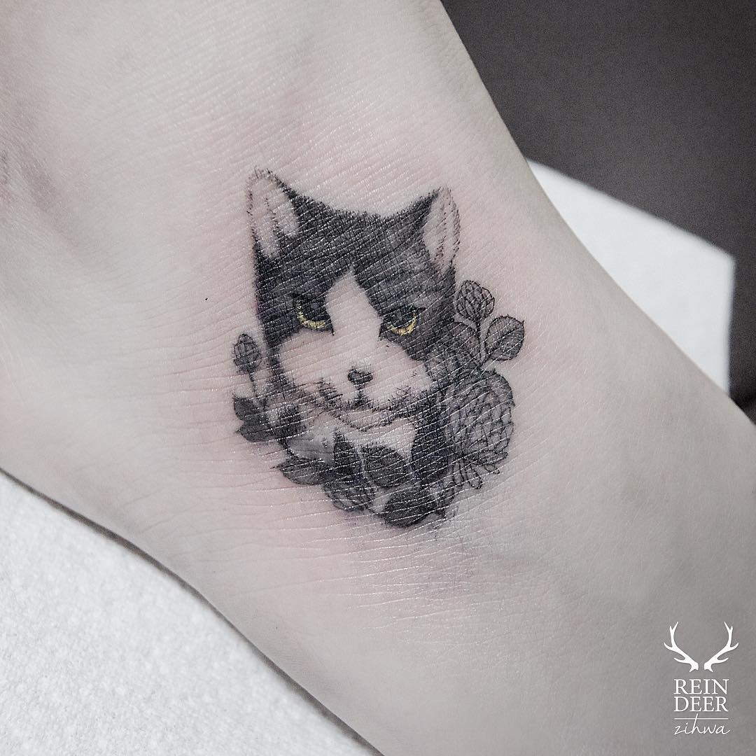 tiny head of a cat tattoo in even tinier flowers