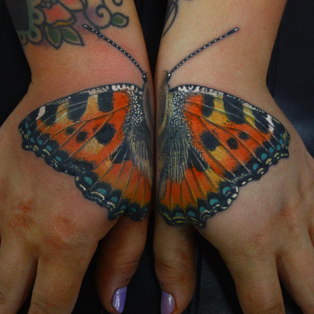 one butterfly tattoo design split in two hand tattoos