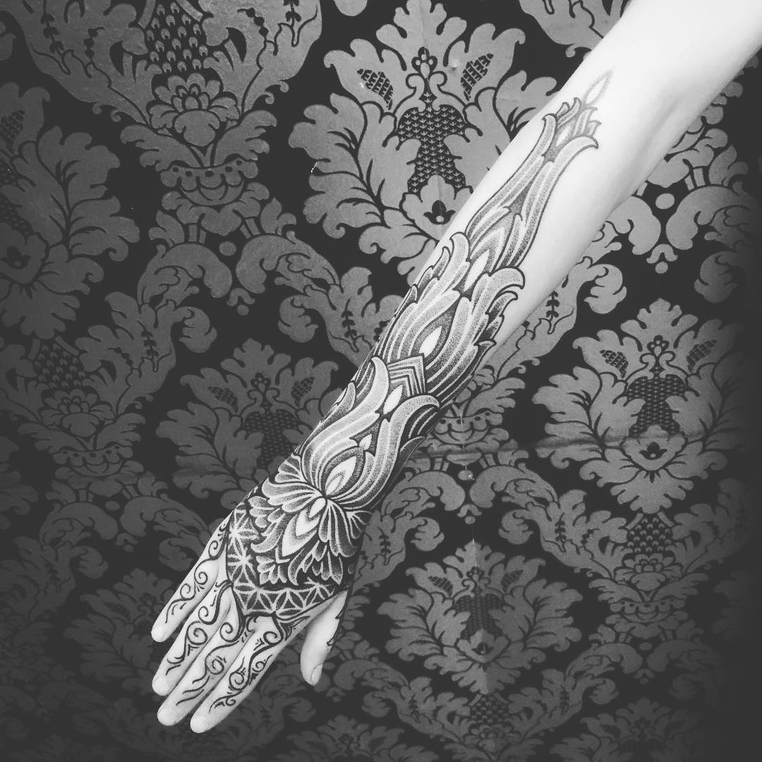 a half sleeve tattoo with lotus and mehendi style ornament