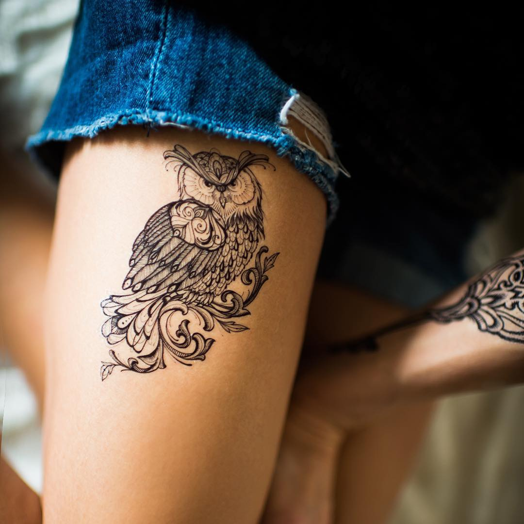 the tattoo of owl on thigh with a thin lines however with some sort of trible style patterns