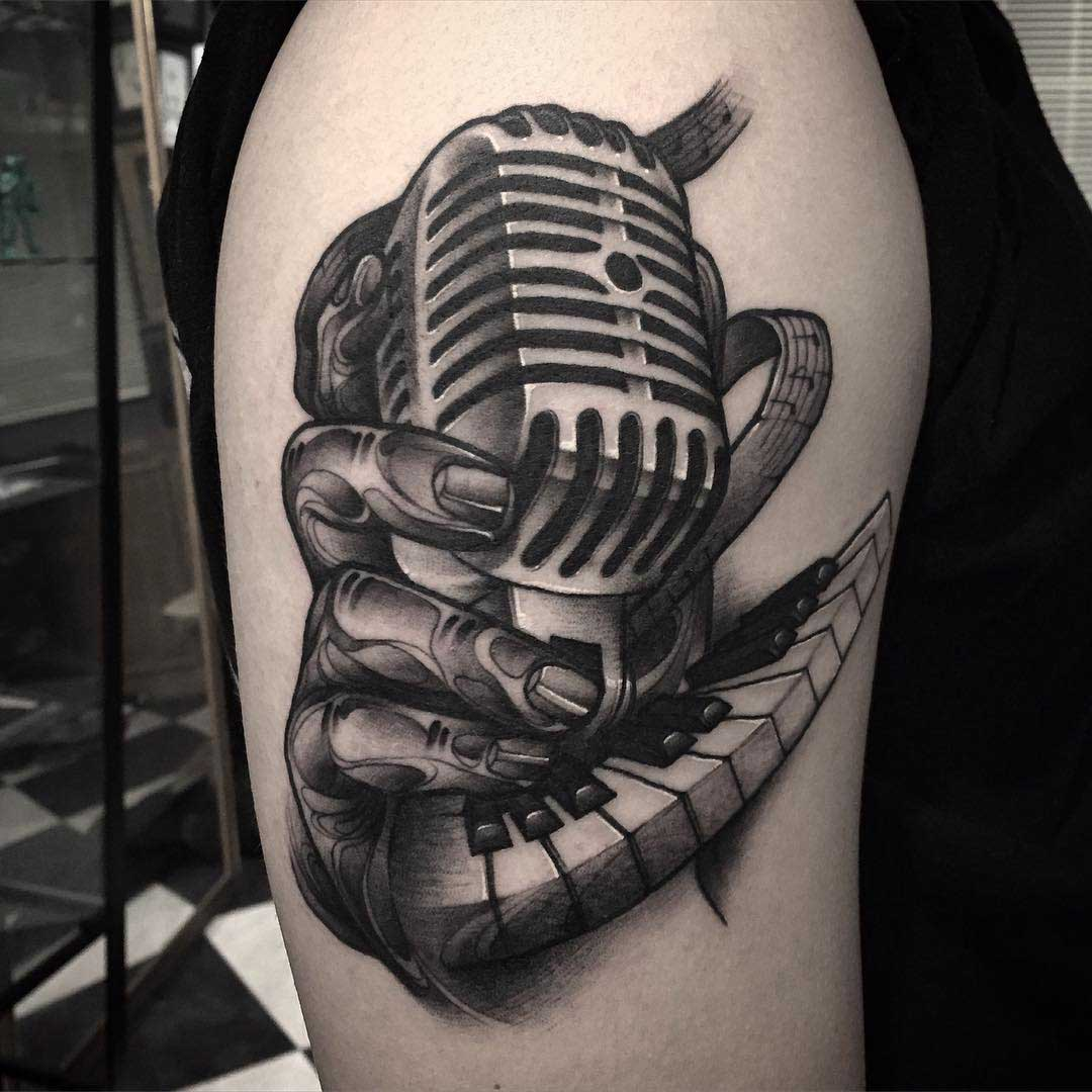 a vintage microphone tattoo on shoulder
