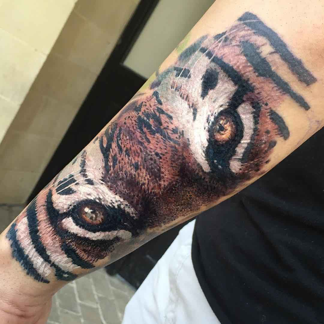 eyes of tiger tattoo on forearm