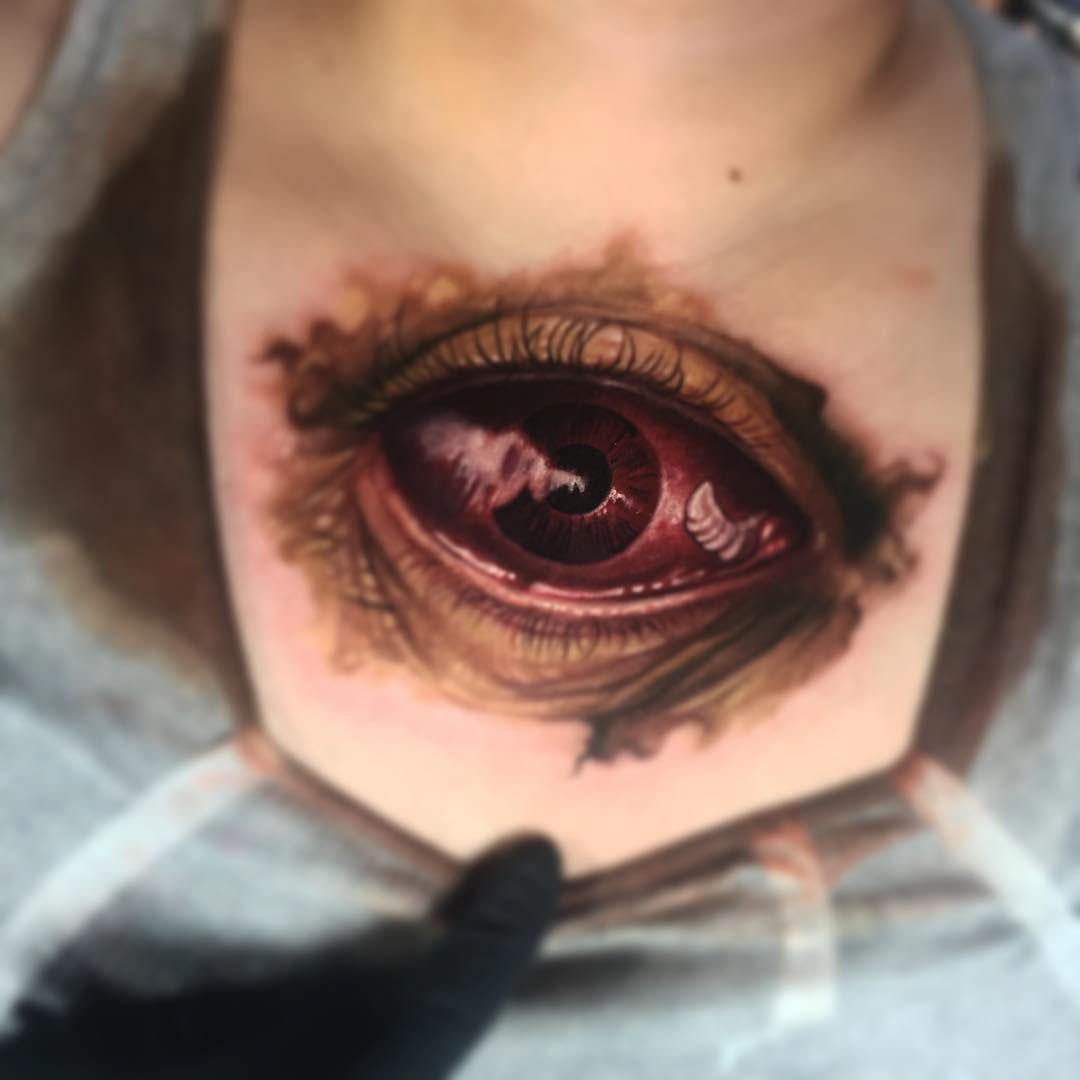 lower neck red eye tattoo