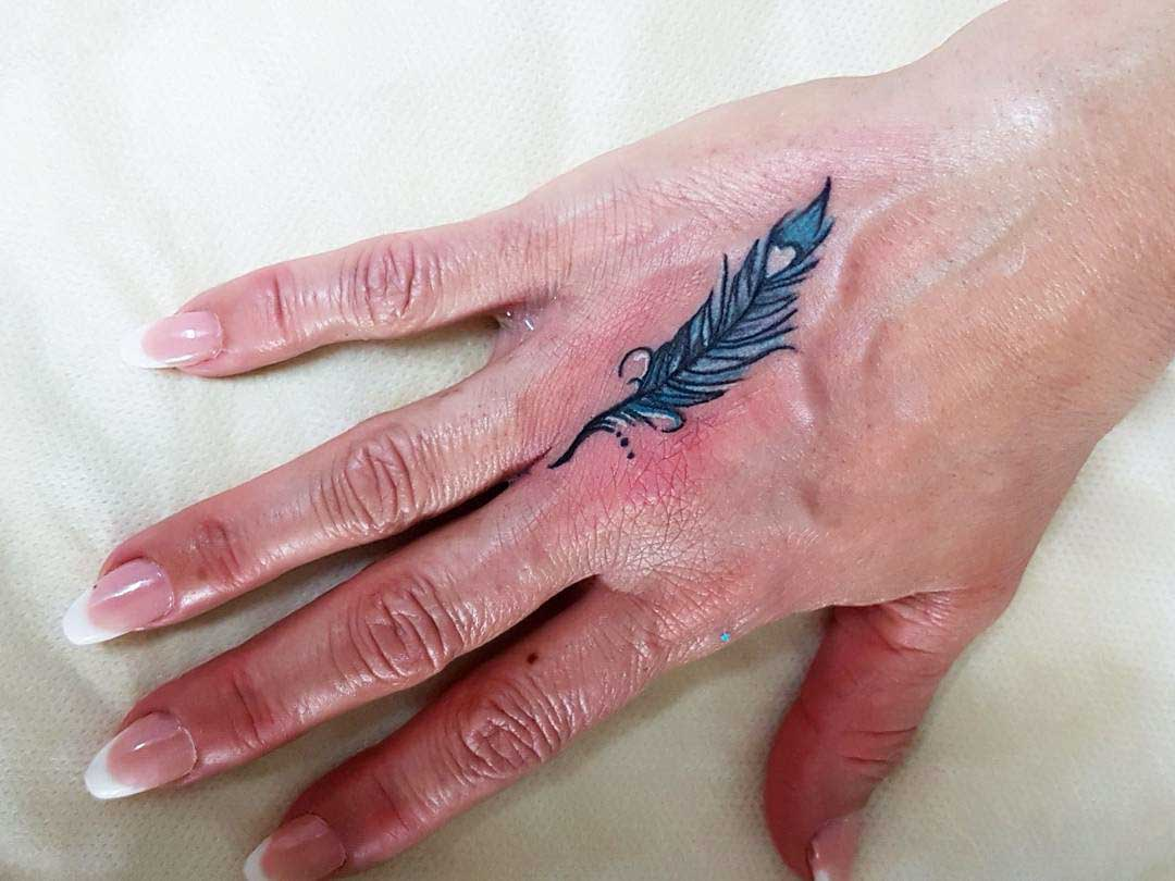 hand tattoo feather