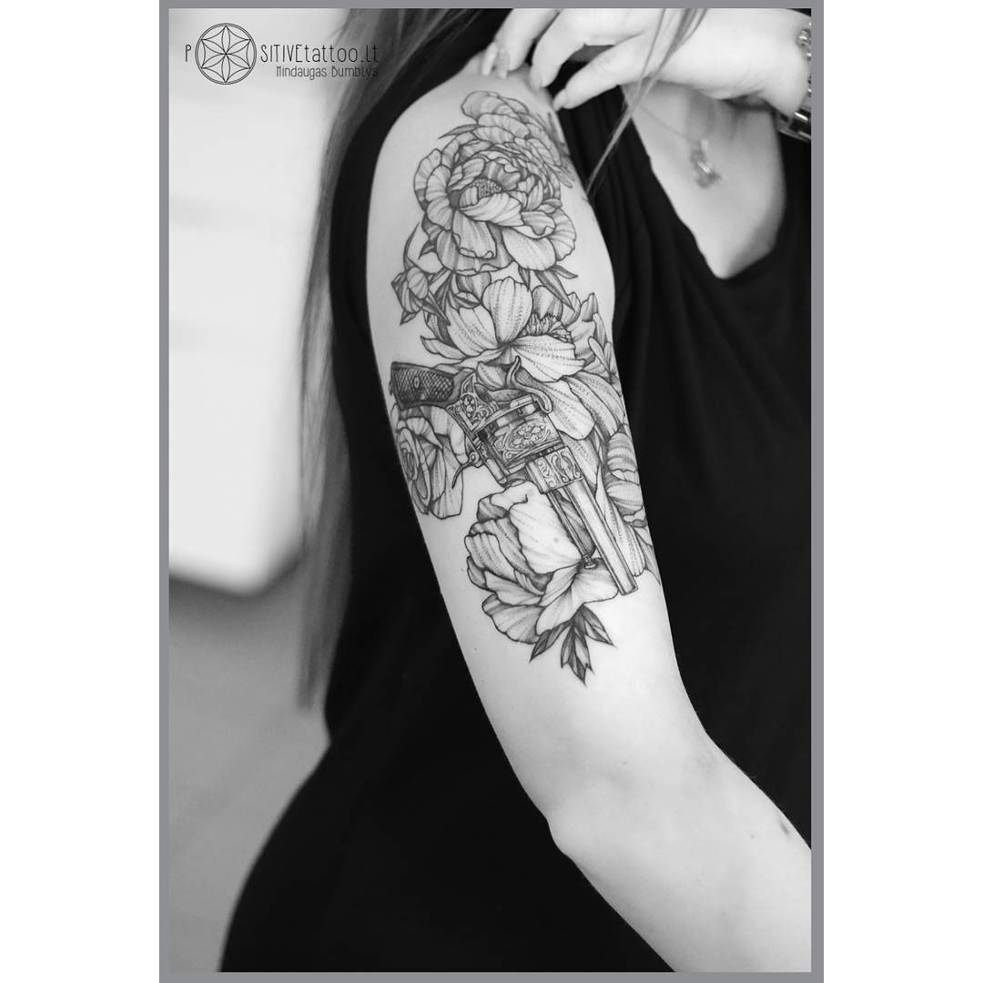 gun and flowers tattoo on shoulder