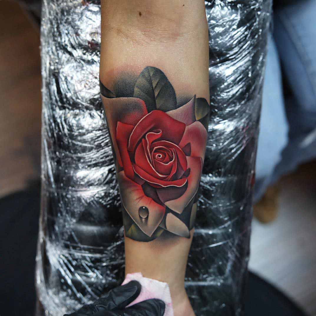 rose tattoo on arm with dew drop