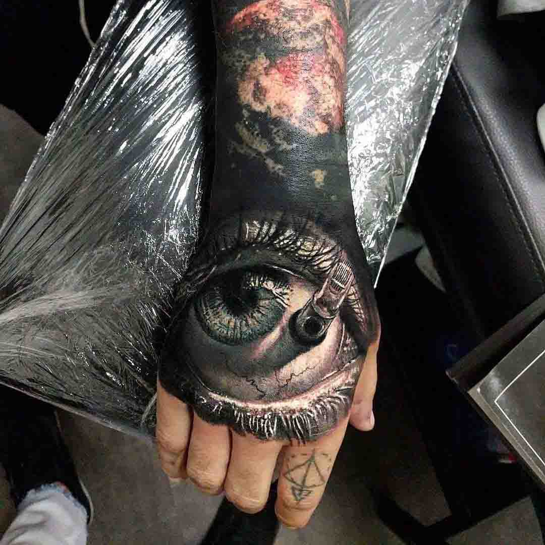 eye tattoo on hand with needles